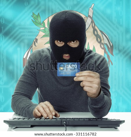 Dark-skinned hacker with credit card in hand and USA states flag on background - Oklahoma - stock photo