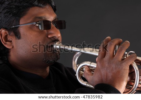 Dark skinned man from India wearing dark glasses and playing a trumpet before a black background