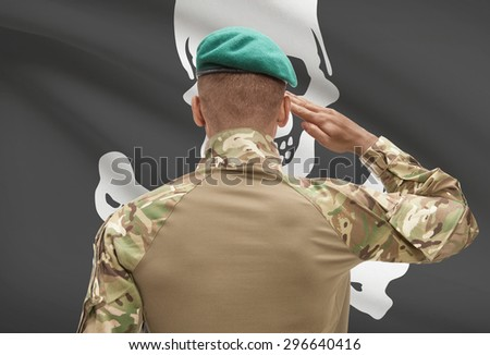 Dark-skinned soldier in hat facing flag series - Jolly Roger - stock photo