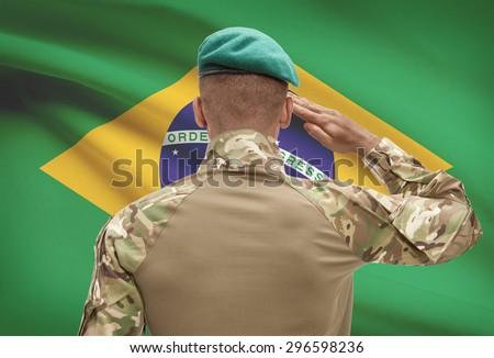 Dark-skinned soldier in hat facing national flag series - Brazil - stock photo