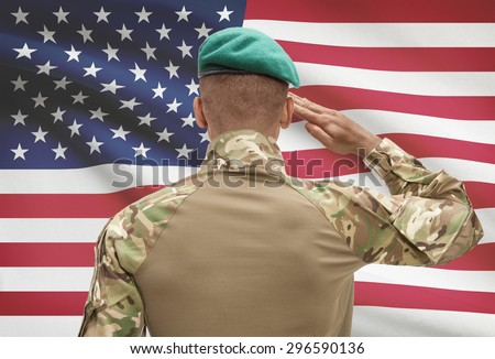 Dark-skinned soldier in hat facing national flag series - United States - stock photo