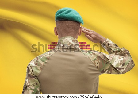 Dark-skinned soldier in hat facing US state flag series - New Mexico - stock photo