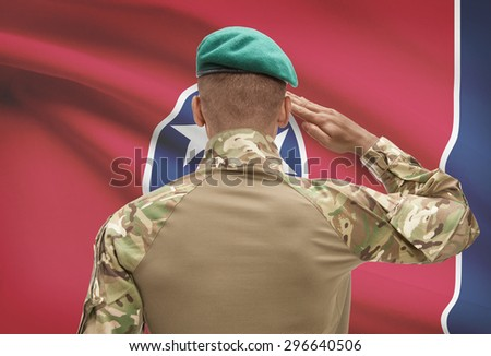 Dark-skinned soldier in hat facing US state flag series - Tennessee - stock photo