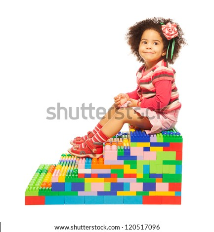 Dark skinned two years old girl on the stairs maid or toy plastic blocks - stock photo