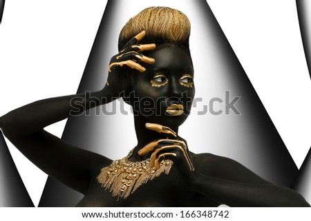 dark-skinned woman with gold decoration on the body.