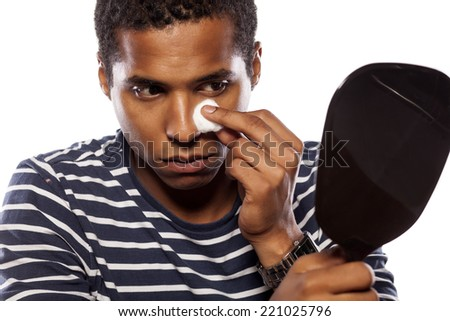 dark-skinned young man cleanse his face with cotton pad - stock photo