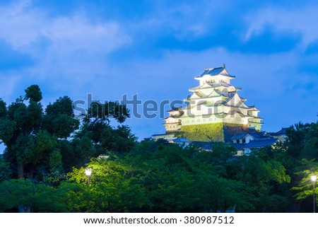 Dark sky behind lighted Himeji-jo, one of 12 remaining original castles, rising above trees at dusk blue hour in Himeji, Japan after 2015 renovations finished. Horizontal copy space