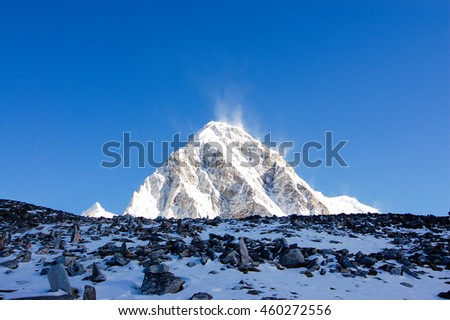 Dark stones spread all over the snowy ground of hillside with Pumori in background on a bright blue sky day.