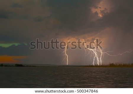 Dark storm clouds and lightning flash on a large lake