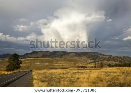 Dark storm clouds over golden grasses of the Lamar Valley, with a road and a car in the distance, in Yellowstone National Park, Wyoming. - stock photo