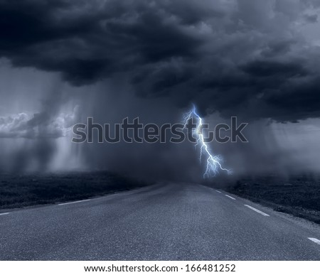 Dark stormy clouds over road - stock photo