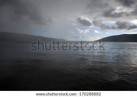 Dark stormy rain cloud in the horizon of a wavy sea - stock photo