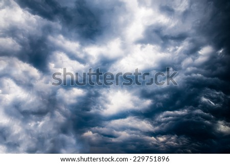 Dark stormy sky with bright spots and really dark clouds - stock photo