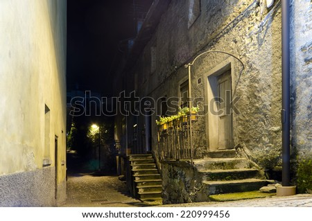 Dark street and house in old italian town, yellow light from the lantern - stock photo