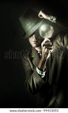 Dark Studio Photo Of A Mystery Man Wearing Retro Business Fashion While Examining A Clue Of Evidence Through A Eye Glass In A Undercover Spy Concept - stock photo