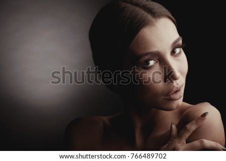 Dark studio portrait of elegant and sexy brunette woman with brown eyes