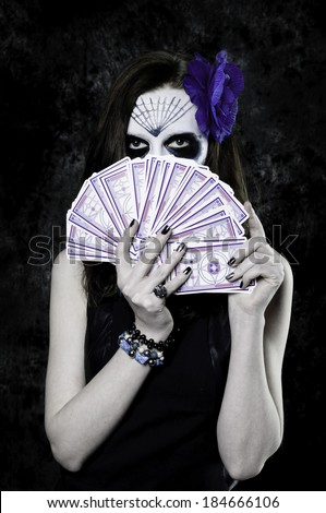 Dark with with dia de los muertos makeup and tarot cards - stock photo