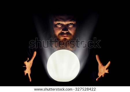 Dark wizard is making magic with the magic crystal. - stock photo