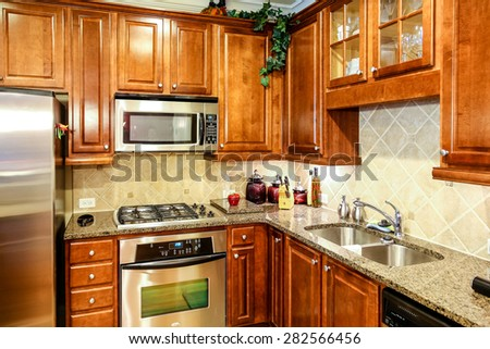Dark wood cabinets with granite countertops and stainless steel appliances - stock photo