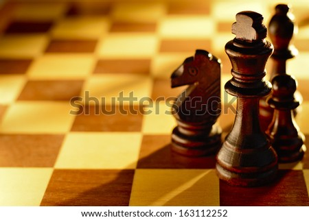 Dark wood chess pieces standing on a chessboard in a low angle beam of light with focus to the king and a large area for copy