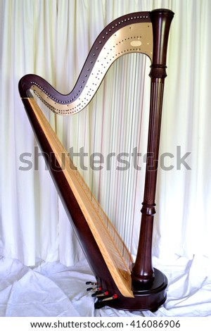 Dark wood concert grand pedal harp against wide curtains