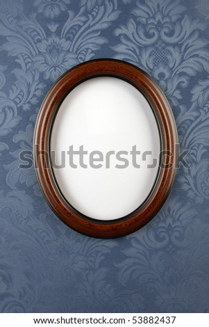 Dark wood oval wall frame shot of vintage blue flocked, floral wallpaper with space for photo to be inserted and room for copy - stock photo