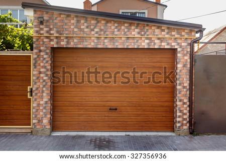 Dark Wooden Garage Door with colored brick wall background - stock photo
