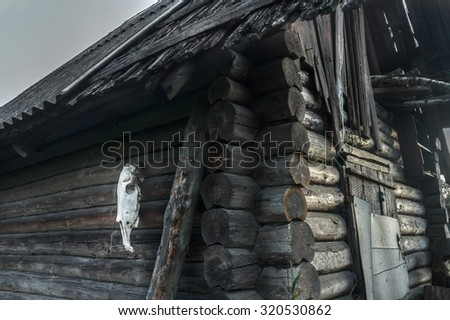 Dark wooden log haunted house with horse skull on gray wall - stock photo