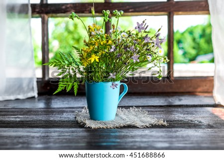 Dark wooden table decorated with bunch of meadow flowers.