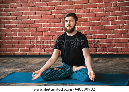 Darkhaired man with a beard wearing black T-shirt and blue trousers doing yoga position on blue matt at wall background, copy space, portrait, lotus asana, padmasana - stock photo