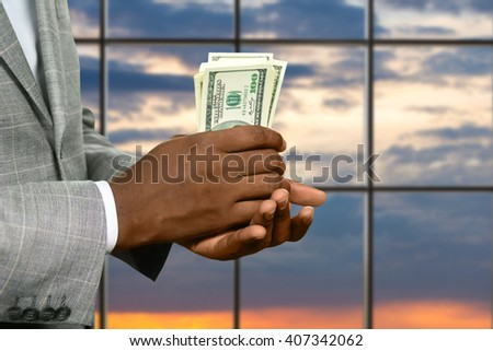 Darkskinned man's hand holding cash. Businessman with dollars at sunrise. Warm up your pocket. Fresh and crispy. - stock photo