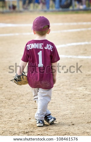 Darling little 4 year old redheaded boy in ball uniform and cap with glove standing on field - stock photo