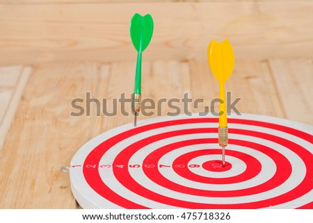 Dart arrow hitting in bulls eye on dartboard