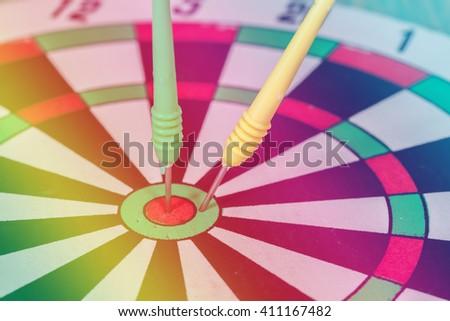 dart arrow hitting in the target center of dartboard - stock photo