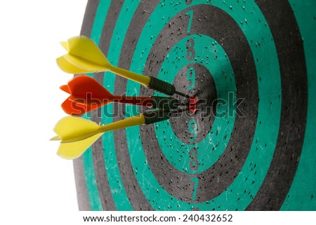 Dart arrows hitting in the center of green dartboard. - stock photo