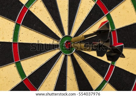 Dart arrows hitting in the target center of dartboard