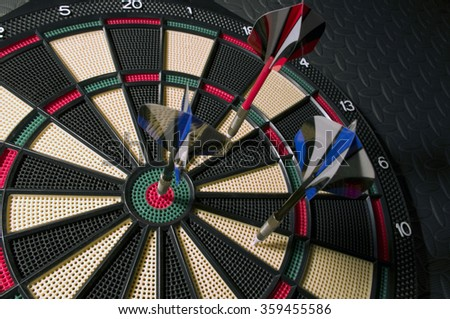 dart board dark background red and blue darts - stock photo