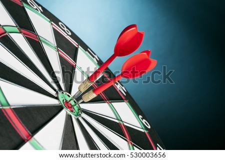 Dart board targeting the center on a  blue background