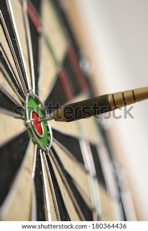 Dart board with dart on bullseye  - stock photo