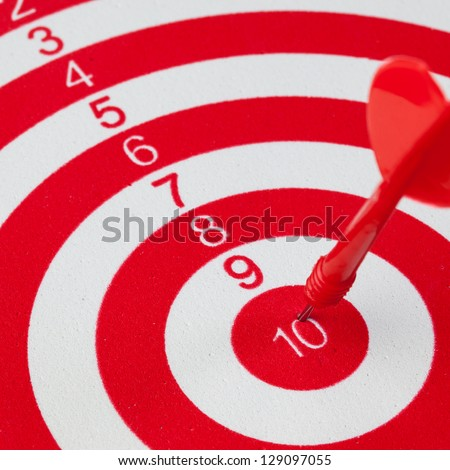 Dart hit maximum score on target in red and white dartboard