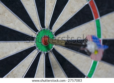 dart in bull's eye of dartboard - focus on bull's-eye