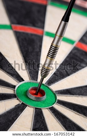 Dart in bulls eye of dartboard - stock photo