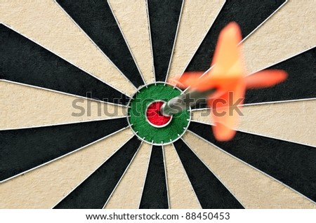 Dart in bulls eye of dartboard