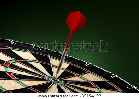 Dart sticks to bullseye on a dart board - stock photo