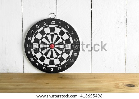 Dartboard on wood table over painted white color wood background