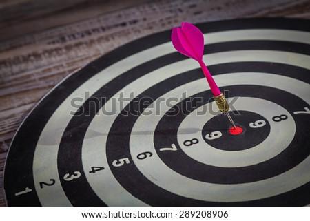 Dartboard on wood wall (Darts Hit Target) - stock photo