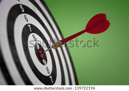 Darts arrow in the target center - stock photo