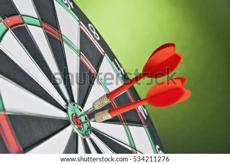 Darts arrows hitting the target center on a green background