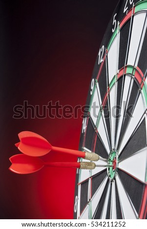 Darts arrows hitting the target center on a red background
