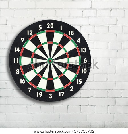 Darts board on a white brick wall with copy space. Classic dartboard with twenty black and white sectors - stock photo